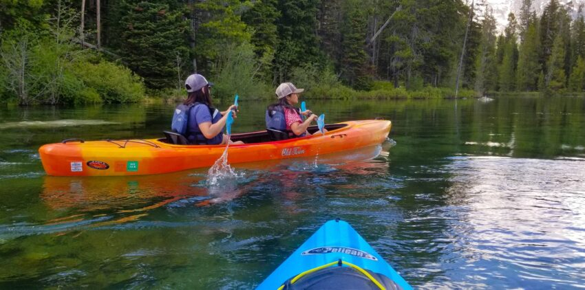 Girls kayaking String Lake, Wyoming. Peruvian woman and Chilean woman.